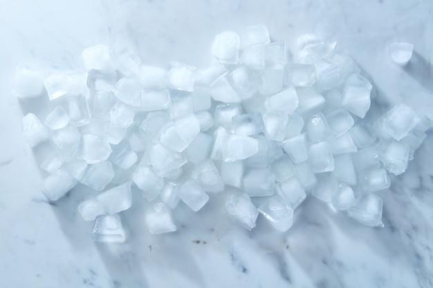 Pulire i cubetti di ghiaccio freddo su uno sfondo di marmo grigio