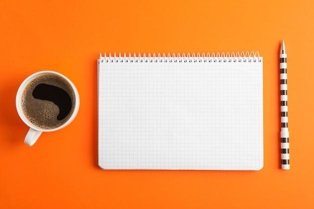 Pulisca il quaderno con la penna e la tazza di caffè sullo spazio di colore