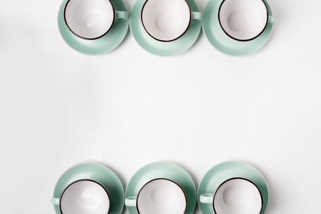 Piatti puliti, cornice per caffè o tè, sfondo. un sacco di tazze e piattini celesti in porcellana elegante in bianco, chiave alta, vista dall'alto e piatto.