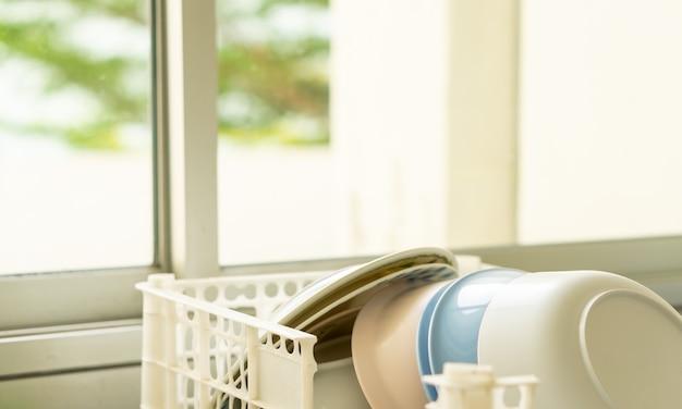 Pulire i piatti impilati nello scolapiatti del bancone del lavello della cucina
