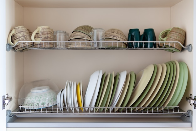 Piatti puliti nei toni del bianco e del verde nell'armadio di essiccazione.