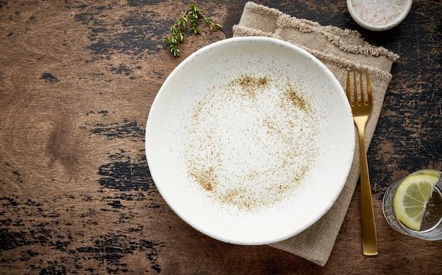 Pulisca il piatto, la forcella e il coltello ceramici bianchi vuoti sulla vecchia tavola scura marrone, copi lo spazio, derisione su