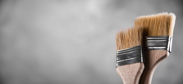 Pulire i nuovi pennelli per dipingere su sfondo grigio cemento sfocato. primo piano con copia spazio vuoto per il testo. banner per la pubblicità.