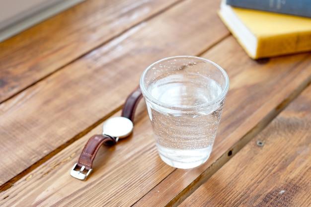 Pulisci un bicchiere d'acqua su un tavolo di legno mentre leggi i libri di lavoro un orologio per ricordarti di prendere regolarmente l'acqua per uno stile di vita sano.