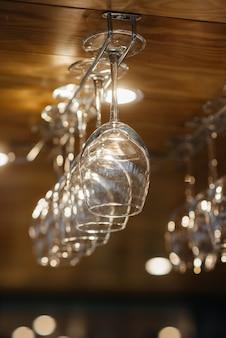 Bicchieri puliti per bevande alcoliche sono appesi sopra il bar in un ristorante moderno