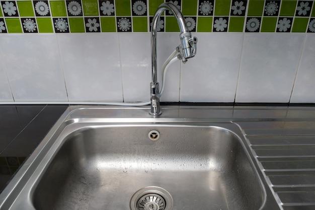 Il lavandino in metallo pulito con il rubinetto cromato dopo il lavaggio sul bancone moderno, all'interno della cucina della casa urbana, vista frontale per lo spazio della copia.