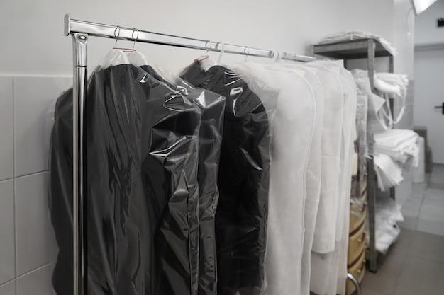Vestiti puliti imballati appesi nell'officina della tintoria