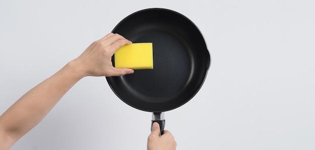 Pulisci la padella. uomo che pulisce la padella antiaderente con una comoda spugna per lavare i piatti.
