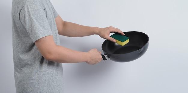 Pulisci la padella, maglietta uomo in colore grigio che pulisce la padella antiaderente con una comoda spugna per piatti.