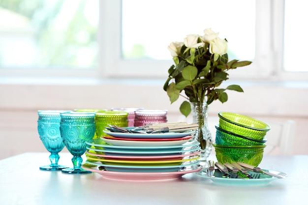 Piatti puliti, bicchieri e posate sul tavolo bianco