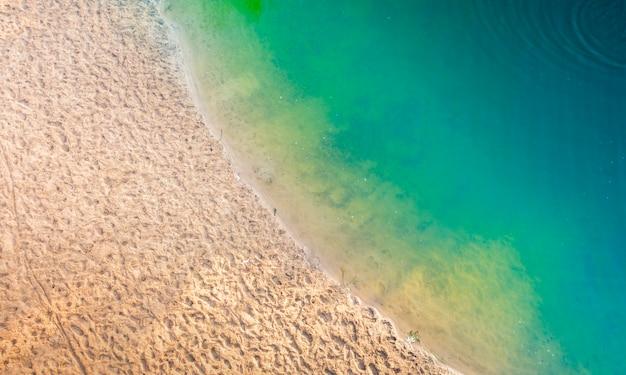 Lettini da spiaggia sabbiosi puliti e acqua turchese. vista dall'alto.