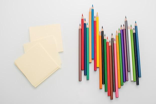 Fogli puliti per appunti e matite colorate sul tavolo bianco.