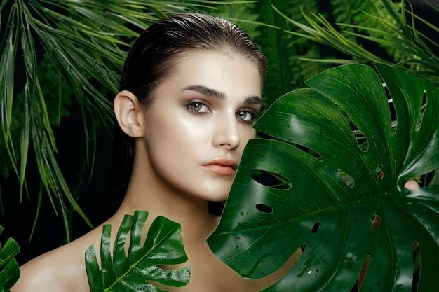 Pulire il concetto di pelle di cosmetologia con la donna vicino a foglie verdi di palma