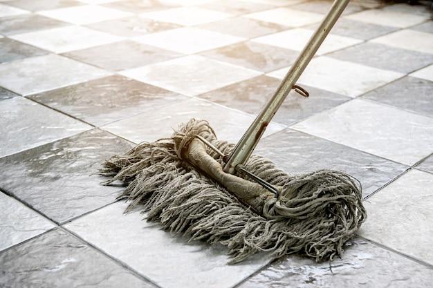 Pulisci i pavimenti in piastrelle con stracci e prodotti per la pulizia dei pavimenti.