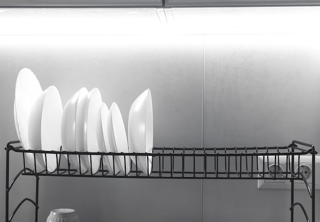 Pulisci i piatti bianchi che si asciugano su uno scolapiatti in metallo su uno sfondo di cucina con luce intensa foto