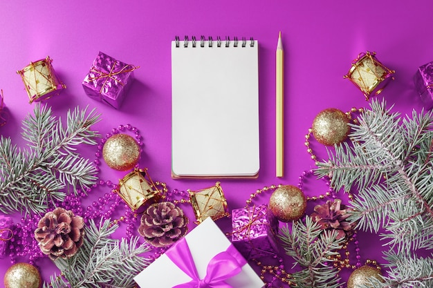 Pulire il blocco note bianco con la matita intorno alle decorazioni di natale sul tavolo viola. pianificazione, lista dei desideri e risoluzione 2021. la vista dall'alto