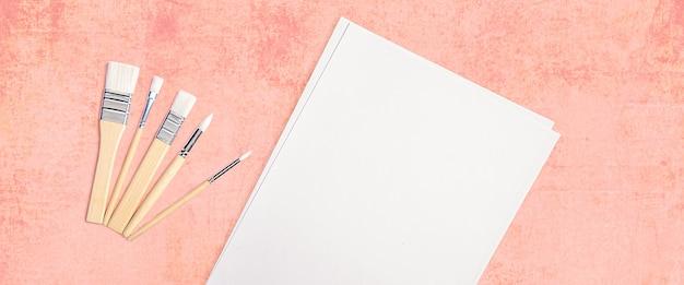 Un foglio bianco pulito e spazzole su uno sfondo rosa con texture con spazio per copiare.