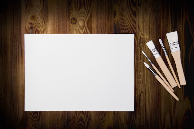 Un foglio bianco pulito e spazzole su uno sfondo con texture di legno con spazio per copiare.