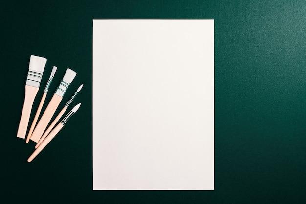 Un foglio bianco pulito e pennelli su uno sfondo verde scuro con spazio per copiare. mock-up, mockup, layout.