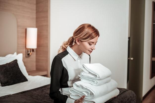 Asciugamani bianchi puliti. giovane governante eccitata dai capelli biondi che si gode l'odore di asciugamani bianchi puliti