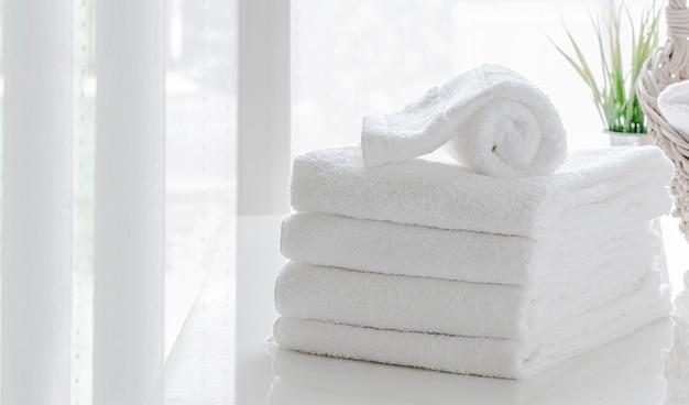 Pulisca gli asciugamani bianchi sulla tavola bianca nella stanza bianca, copi lo spazio.