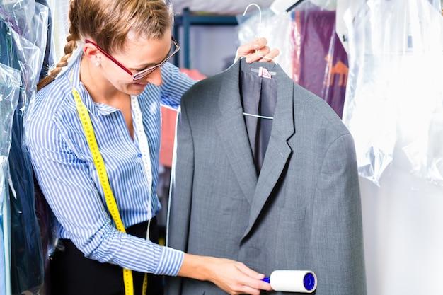 Pulitore in lavanderia che controlla i vestiti puliti