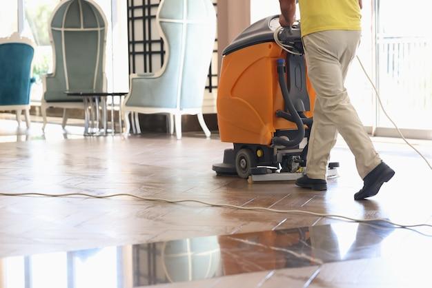 Pavimento di lavaggio più pulito della hall dell'hotel con primo piano della macchina