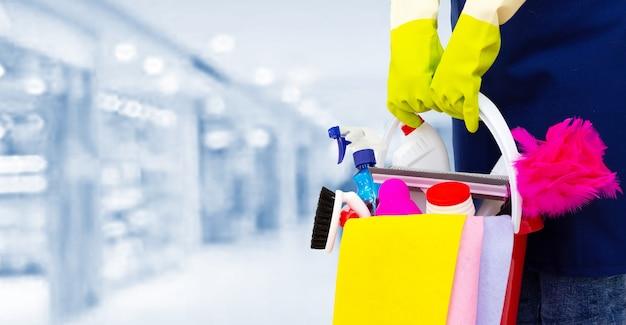 Detergente con prodotti per la pulizia nel centro commerciale. una donna delle pulizie si trova su uno sfondo sfocato con prodotti per la pulizia.