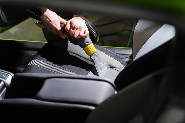 Pulizia auto salone di lavaggio a secco con aspirapolvere. uso professionale di un aspirapolvere a vapore per rimuovere le macchie