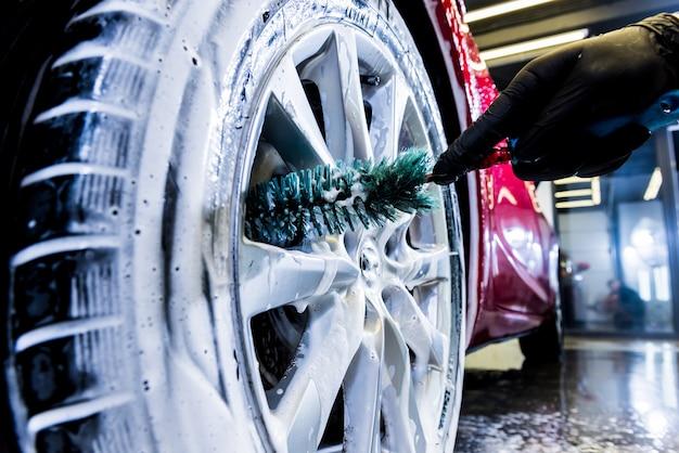 Pulizia della ruota dell'auto con una spazzola e acqua.