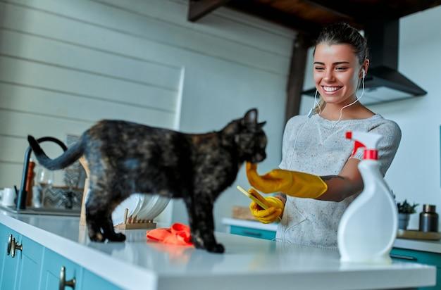 Concetto di pulizia. una donna attraente in abiti casual e guanti protettivi ascolta musica con le cuffie e gioca con un gatto, e pulirà la polvere con uno straccio e uno spray.
