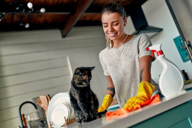 Concetto di pulizia. una donna attraente in abiti casual e guanti protettivi ascolta musica con le cuffie e gioca con un gatto mentre pulisce la polvere sul tavolo con uno straccio e uno spray.