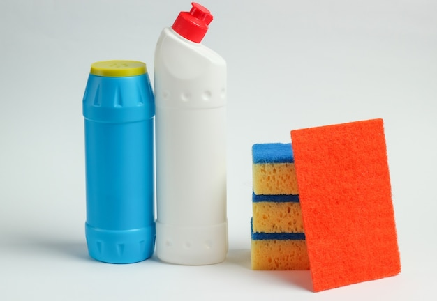 Concetto di pulizia. bottiglie di detersivo, spugne su sfondo bianco