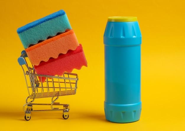 Concetto di pulizia. carrello della spesa con bottiglia di detersivo, spugne su sfondo giallo