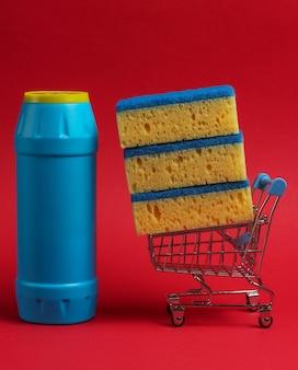 Concetto di pulizia. carrello della spesa con flaconi di detersivi, spugne su fondo rosso