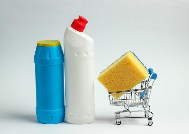 Concetto di pulizia. carrello della spesa con bottiglie di detersivo, spugne su sfondo bianco