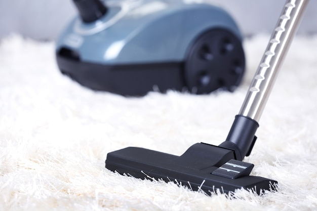 Concetto di pulizia - aspirapolvere sul tappeto bianco morbido, da vicino
