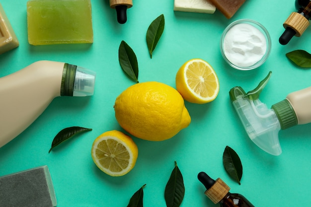 Concetto di pulizia con strumenti di pulizia ecologici e limoni su fondo isolato menta