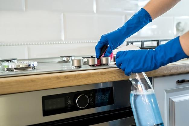 Concetto di pulizia. la donna lava e pulisce in cucina.