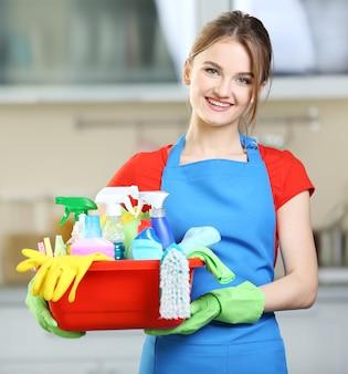 Concetto di pulizia. la giovane donna tiene il bacino con i liquidi di lavaggio e gli stracci nelle mani