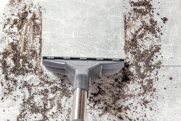 Pulizia del pavimento sporco con aspirapolvere in soggiorno, aspirapolvere.