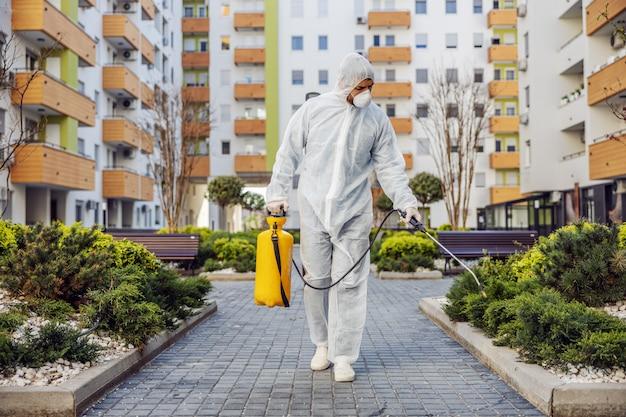 Pulizia e disinfezione all'esterno intorno agli edifici, l'epidemia di covid-19. squadre di sessione per gli sforzi di disinfezione. prevenzione delle infezioni e controllo dell'epidemia. e vestito e maschera.