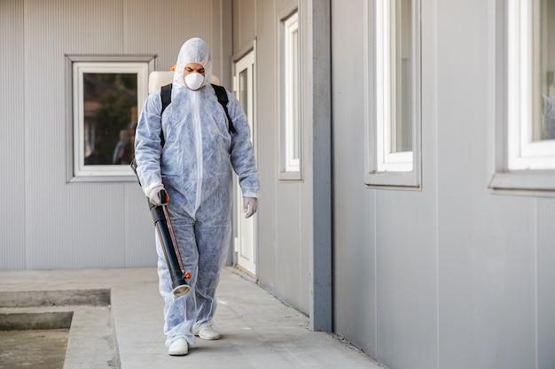 Pulizia e disinfezione all'esterno intorno all'edificio: tuta e maschera.