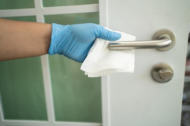 Pulizia della maniglia della porta con panno e tessuto in ufficio e a casa per proteggere il covid 19 coronavirus