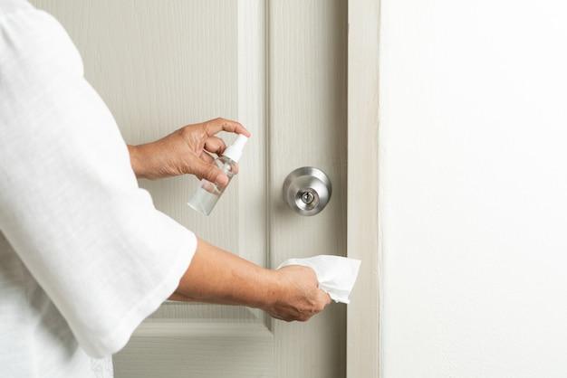 Pomello della porta di pulizia con spray alcolico per la prevenzione del coronavirus covid-19