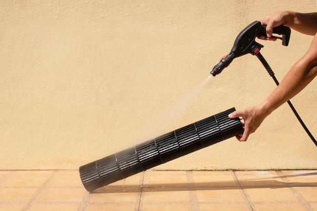 Pulizia delle pale del ventilatore dell'aria condizionata con pompa dell'acqua