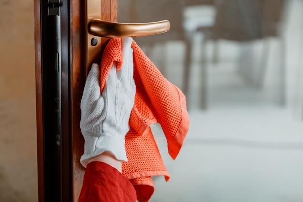 Pulizia della maniglia della porta anteriore con detergente alcolico antibatterico. la donna domestica in guanti bianchi pulisce la manopola della porta dallo straccio del panno. nuovo normale coronavirus covid 19 nella disinfezione delle superfici.