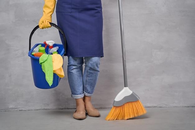 Pulire la casa. ritagliata colpo di donna in uniforme e guanti di gomma gialli che tengono scopa e secchio diversi prodotti per la pulizia mentre in piedi contro il muro grigio. pulizie, lavori domestici, pulizie