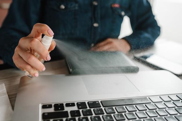 Pulizia della tastiera del computer portatile per eliminare lo spray antibatterico da germi.