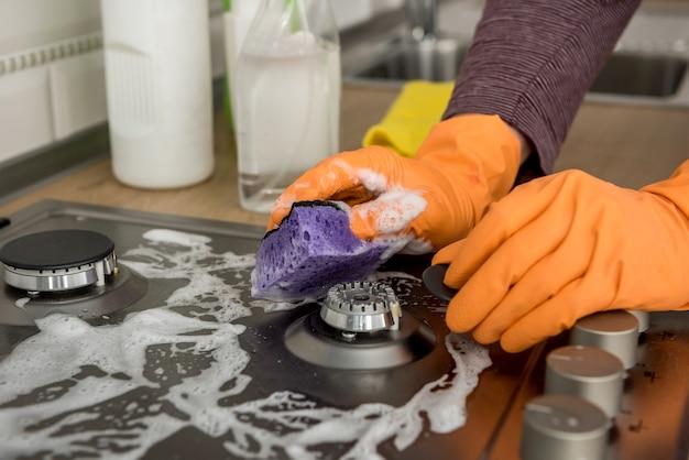 Pulizia in cucina con pietra a gas con schiuma e spugna. apparecchiature domestiche per uno stile di vita salutare